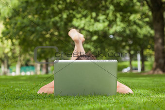 Young woman lying on grass in front of laptop