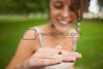Close up of a blurred woman gently holding a ladybug