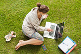 Female student using laptop with books at the park