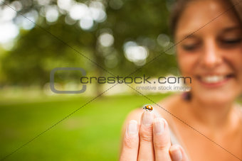 Smiling blurred woman gently holding a ladybug