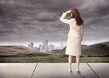 Brunette businesswoman in front of cloudy sky