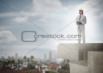 Architect with hard hat and clipboard against the sky and cityscape