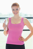 Woman with water bottle standing in fitness studio