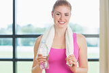 Portrait of a woman with towel around neck holding water bottle in fitness studio