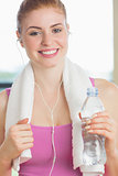 Woman with towel around neck holding water bottle in fitness studio
