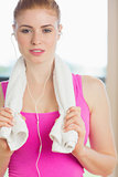 Woman with towel around neck listening to music in fitness studio