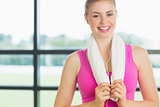Smiling woman with towel around neck listening to music in fitness studio