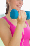 Mid section of a woman exercising with dumbbells