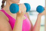 Mid section of a woman exercising with dumbbells in fitness studio