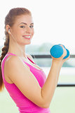 Fit young woman exercising with dumbbells in fitness studio
