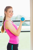 Side view of a fit woman exercising with dumbbells in fitness studio