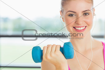 Fit woman exercising with dumbbells in fitness studio