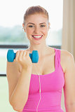 Cheerful woman exercising with dumbbells in fitness studio