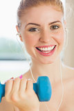 Close up portrait of a fit woman exercising with dumbbells