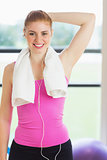 Fit woman with towel around neck at fitness studio