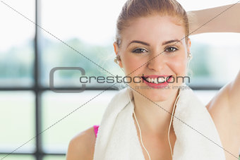 Woman with towel around neck listening to music
