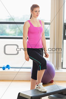 Fit woman on step in abright fitness studio