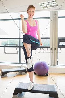 Beautiful woman performing step aerobics exercise