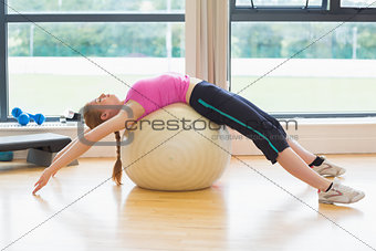 Fit woman stretching back on exercise ball in fitness studio