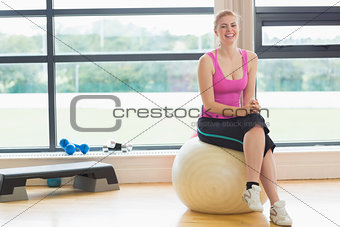 Cheerful woman sitting on exercise ball in fitness studio