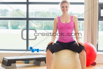 Beautiful woman sitting on exercise ball in fitness studio