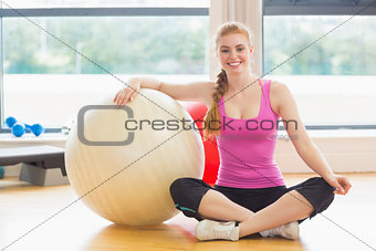 Fit beautiful woman with exercise ball in fitness studio