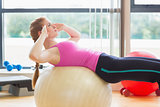 Fit woman working out with exercise ball in fitness studio