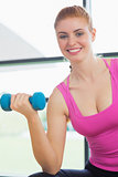 Portrait of a fit woman exercising with dumbbells