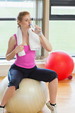Fit woman sitting on exercise ball and drinking water