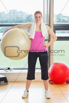 Fit beautiful young woman carrying exercise ball