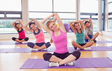Portrait of fitness class and instructor stretching hands on yoga mats