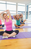 Fitness class and instructor stretching hands on yoga mats