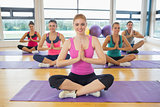 Class and instructor sitting in Namaste position on exercise mats
