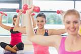 Fitness class and trainer lifting dumbbells