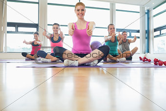 Class and instructor gesturing thumbs up on yoga mats