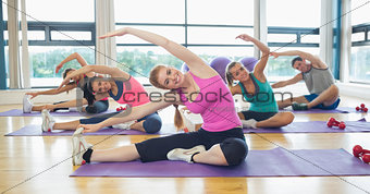 Class and instructor doing stretching pilate exercises