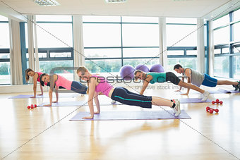 Side view of trainer with class doing push ups