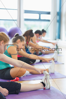 Fitness class and instructor stretching legs