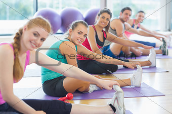 Portrait of fitness class and instructor stretching legs