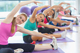 Fitness class and instructor doing stretching exercise on yoga mats