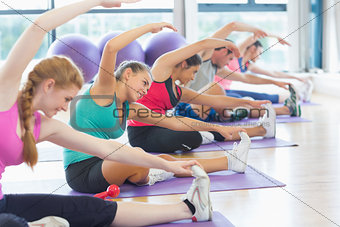 Fitness class and instructor doing stretching exercise