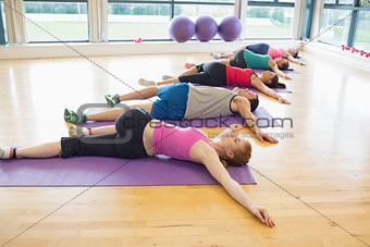 Full length of sporty people stretching on mats at yoga class