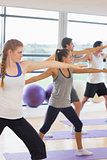 Sporty people stretching hands at yoga class in fitness studio