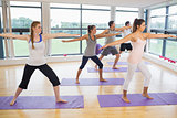 Full length of sporty people stretching hands at yoga class
