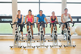 Five determined people working out at spinning class