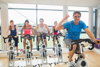 Happy man teaches spinning class to four people