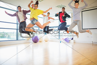 Fit people jumping in exercise room