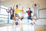 Fit people jumping in bright exercise room