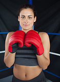 Beautiful woman in red boxing gloves in the ring