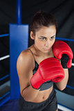 Determined woman in red boxing gloves
